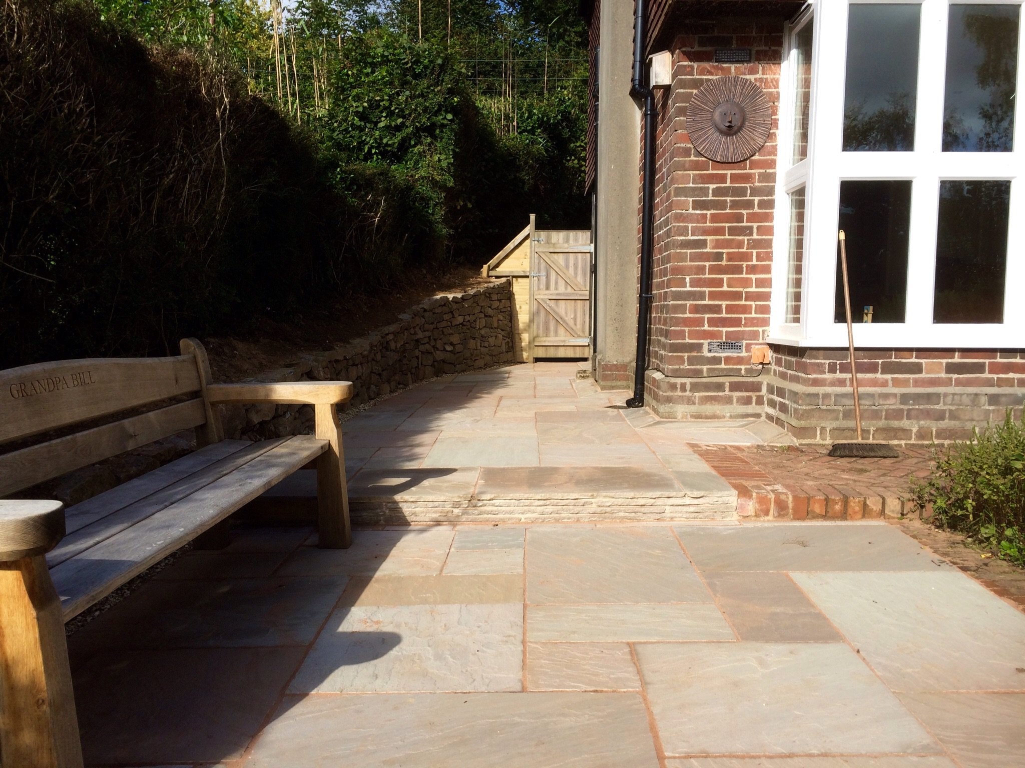 Sandstone paving and drystone wall completed with gate.