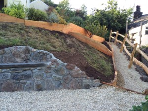 stone bank and seat with larch revetments and paling fencing.